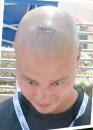 Zappos CEO Tony Hsieh shows off his company spirit with a shaved head and tattoo